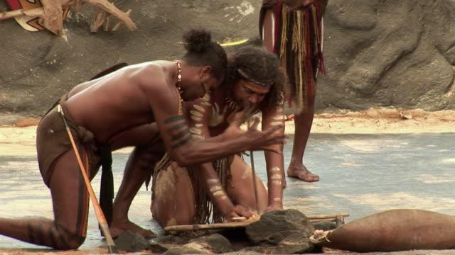 MS Aboriginal man lighting fire, kneeling around wood lined with straw, Queensland, Australia