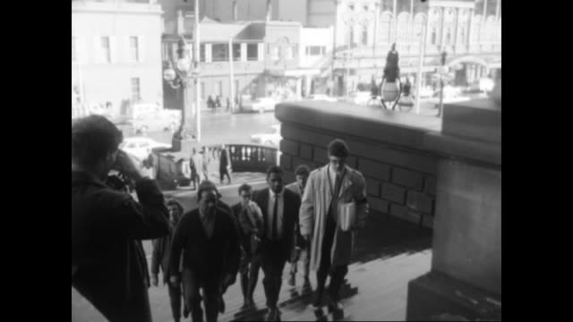stockvideo's en b-roll-footage met aboriginal man with mr harry penrith aboriginal rights activist and author and unknown white men walking into victorian parliament buildings carrying... - social justice concept