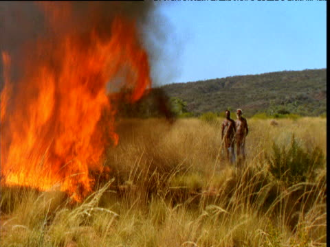 Aboriginal men watch burning fire on grassland in outback, Northern Territory, Australia