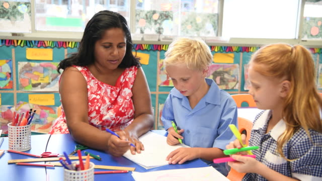 Aboriginal primary school teacher working with boy and girl at their desk