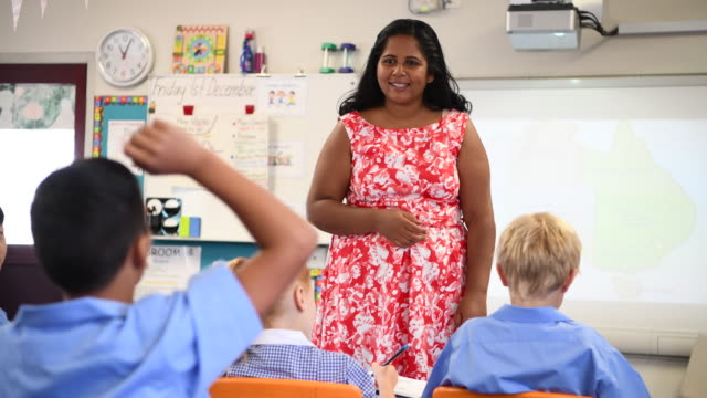 Aboriginal school teacher asking the class questions with a map of Australia on the whiteboard