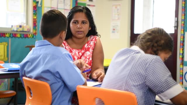 Aboriginal school teacher talking to school boy in classroom at desk