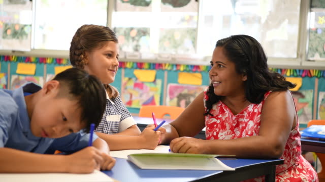 aboriginal teacher smiling and talking to female pupil - classroom stock videos & royalty-free footage