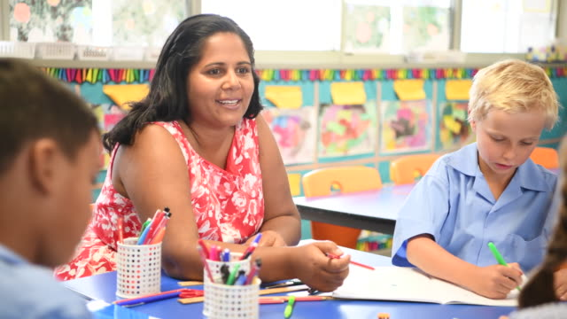 Aboriginal teacher talking and smiling towards primary school children in art class