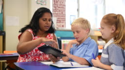 Aboriginal teacher using digital tablet with young boy and girl