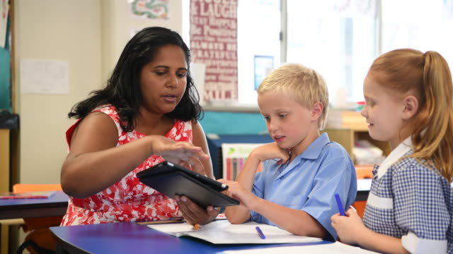 aboriginal teacher using digital tablet with young boy and girl - classroom stock videos & royalty-free footage