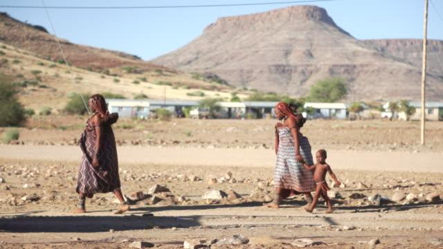 MS Aboriginal woman and children walking down rural street / Bergsig, Kunene, Namibia