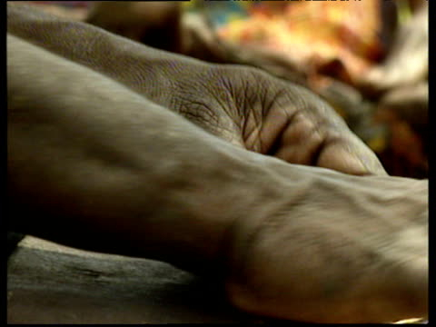 Aborigine hands kneed fibres onto legs making string