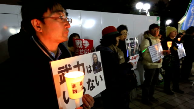 "about 120 people carrying signs saying ""i am kenji"" and other slogans honored journalist kenji goto in tokyo on february 1 a year after his execution... - isis execution stock videos & royalty-free footage"
