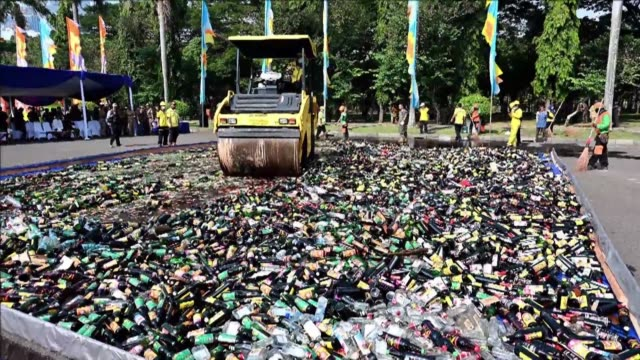 about 18000 bottles of bootleg alcohol are crushed by a steamroller in muslim majority indonesia's capital monday as police warned tipplers off booze... - steamroller stock videos and b-roll footage