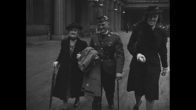 about 30 military personnel stand around in courtyard of buckingham palace talking / major r.c.h. durnford of vancouver walks toward camera with wife... - sergeant stock videos & royalty-free footage