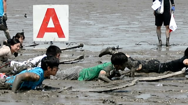 about a thousand people got plastered in mud from head to toe during an outlandish athletic festival held on the tidal flat of the ariake sea here on... - ariake sea stock videos and b-roll footage