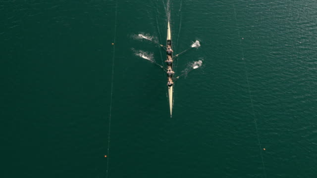 vídeos de stock e filmes b-roll de aerial above a coxless four gliding across a lake - classificados