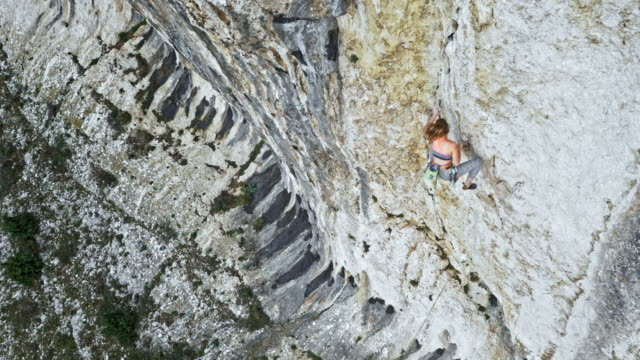 AERIAL Above a female rock climber climbing up a cliff