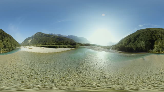 AERIAL VR 360: Above a fisherman fly fishing in a river in sunshine