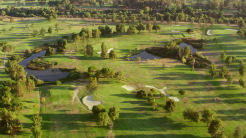 aerial above a golf course in san fernando valley in sunshine - green golf course stock videos & royalty-free footage