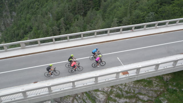 aerial above a group of road cyclists riding across a viaduct - tracking shot stock videos & royalty-free footage