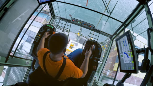 ld above a male crane operator looking down while placing a container onto the ship - attrezzatura industriale video stock e b–roll