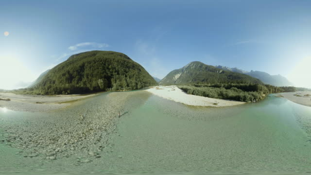 AERIAL VR 360: Above a man fly fishing while standing in a river in sunshine