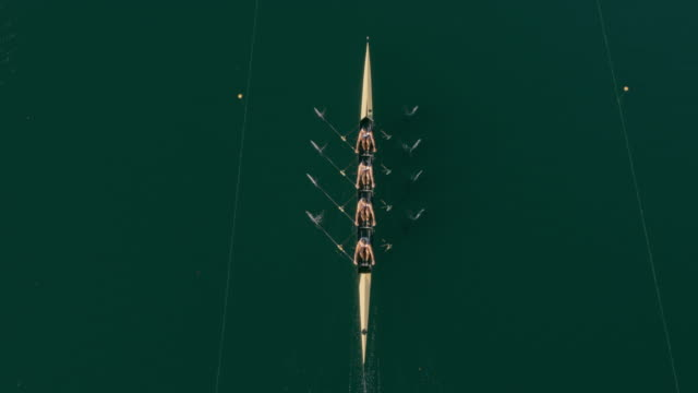 aerial above a quad scull gliding across a lake - four people stock videos & royalty-free footage