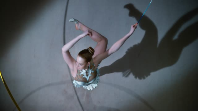 slo mo ld above a rhythmic gymnast performing a pirouette with a golden ribbon in her hand - pirouette stock videos and b-roll footage