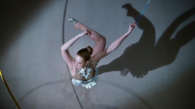 vídeos de stock, filmes e b-roll de slo mo ld acima de um ginasta rítmico que executa um pirueta com uma fita dourada em sua mão - pirouette