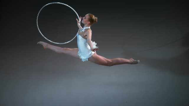 slo mo ld above a rhythmic gymnast performing a split leap while rotating her hoop in one hand - leotard stock videos & royalty-free footage