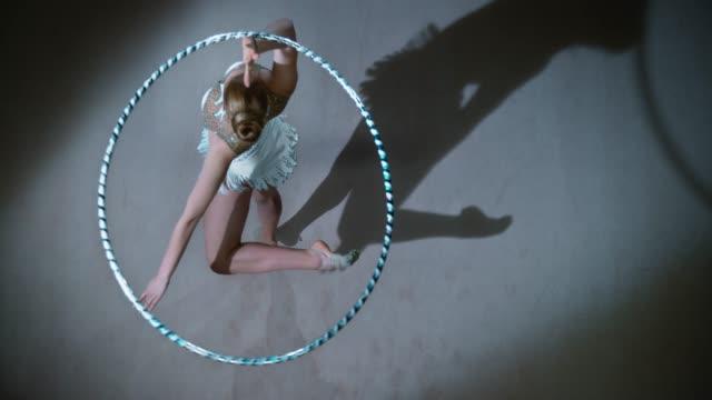 slo mo ld sopra una ginnasta ritmica che ruota mentre ruota un cerchio sopra la testa - acrobata video stock e b–roll