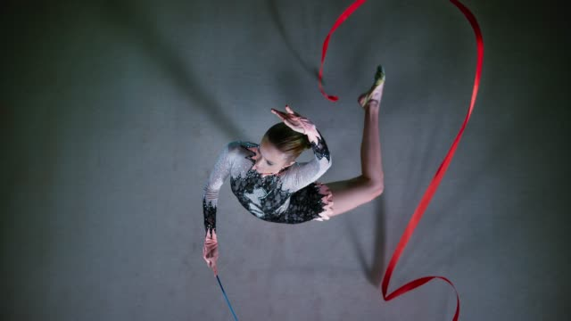 slo mo ld above a rhythmic gymnast pivoting while swirling her red ribbon - flexibility stock videos & royalty-free footage