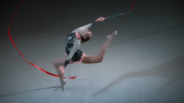 slo mo speed ramp ld above a rhythmic gymnast swinging a red ribbon above her head while performing a stag leap - holding stock videos & royalty-free footage