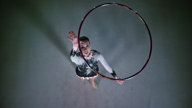slo mo ld above a rhythmic gymnast throwing a hoop in the air and pivoting before catching it - artista di spettacolo video stock e b–roll