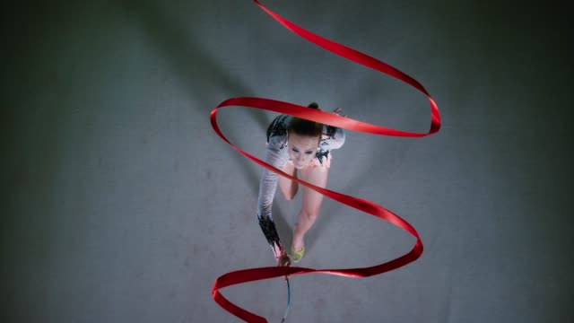 SLO MO LD Above a rhythmic gymnast walking across the floor while swirling a red ribbon