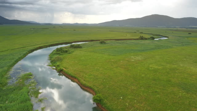 aerial above a river in the cloudy marsh - hill stock videos & royalty-free footage