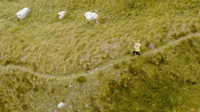 Antenne über ein senior Läufer läuft über eine Wiese hoch in den Bergen