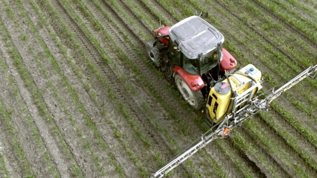 aerial above a tractor spraying crops with a linkage sprayer - insecticide stock videos & royalty-free footage