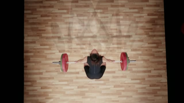 ld above a young female lifter lifting the barbell above her head with a snatch lift - sollevamento pesi video stock e b–roll