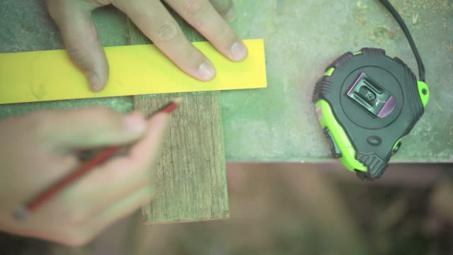 above angle of measuring and hand sawing wood on a work bench - work tool stock videos & royalty-free footage