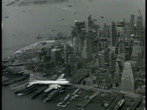 commercial passenger douglas dc-6 airplane flying over east river w/ lower manhattan, new york city below. - east river new york city stock videos & royalty-free footage