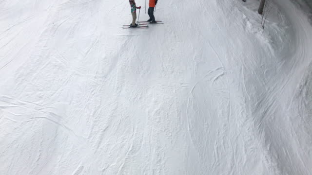 Above footage from the ski lift of couple waving on the ski piste