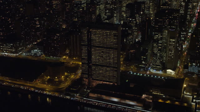 above new york's east river at night, un building in foreground. shot in november 2011. - artbeats stock-videos und b-roll-filmmaterial