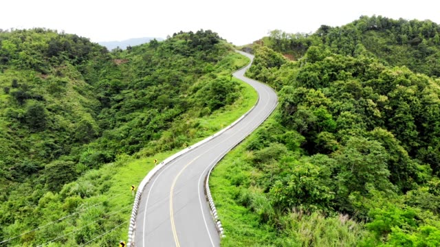 above of asphalt highway through on top of valley with tropical rainforest - curve stock videos and b-roll footage