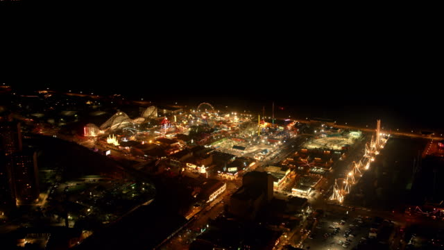 aerial above the amusement park in coney island, ny at night - coney island stock videos & royalty-free footage