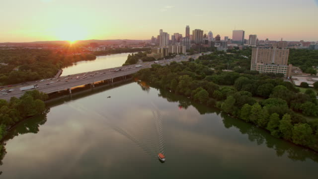 aerial above the colorado river in austin, tx, at sunset - austin texas video stock e b–roll