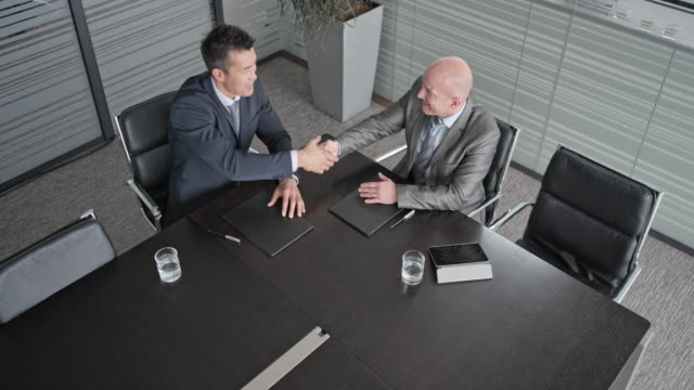 ld above the conference table where an asian and a caucasian businessman are talking and shaking hands - agreement stock videos and b-roll footage
