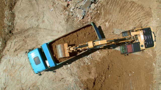 vídeos de stock e filmes b-roll de aerial above the construction site with the excavator loading dug out soil onto a truck - maquinaria de construção