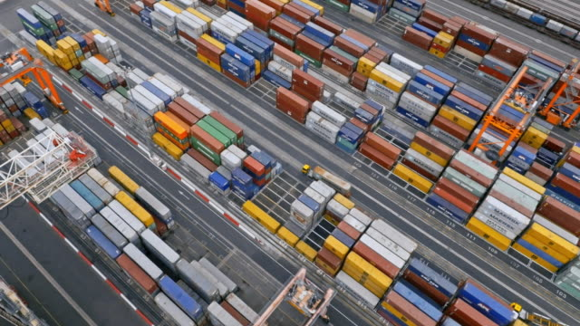 aerial above the cranes and stacks of containers at the container port - trucks in a row stock videos & royalty-free footage