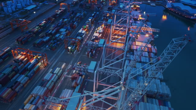 aerial above the cranes at the container port in the evening - stationary stock videos & royalty-free footage