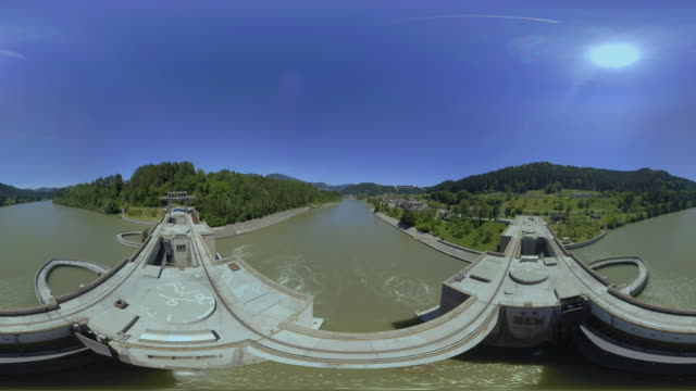 AERIAL VR 360: Above the dam of the hydroelectric power plant in sunshine