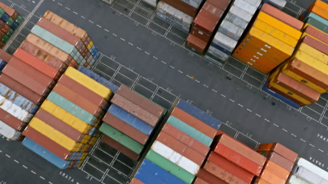 aerial above the high stacks of neatly stacked cargo containers at the terminal - forklift truck stock videos and b-roll footage