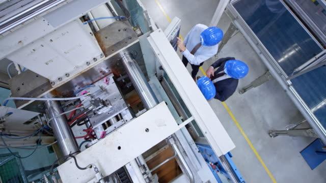 vidéos et rushes de cs au-dessus de l'ingénieur masculin et de deux représentants d'acheteur discutant du panneau de commande de la machine dans l'usine - crane construction machinery